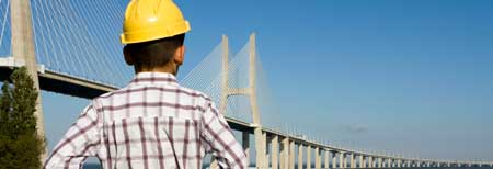 Engineer with yellow helmet looks at the bridge that goes over the water. With a link to the home page.