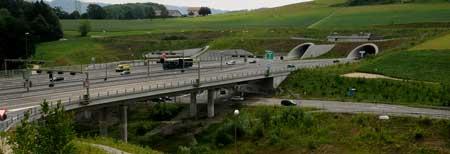 Eine Autobahn auf einer Brücke die in ein Tunnel führt. Mit einem Link auf die Startseite.